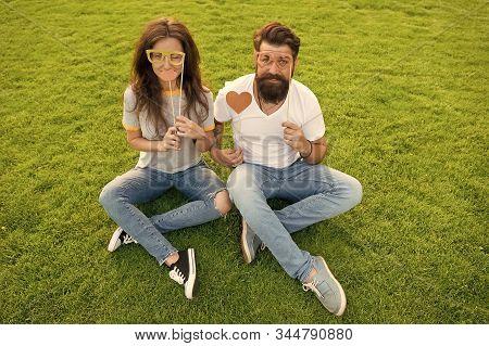 Spreading love. Romantic couple having photobooth fun on green grass. Sensual girlfriend and boyfriend having romantic relationship. Romantic love of bearded man and sexy woman. Romantic partnership. stock photo