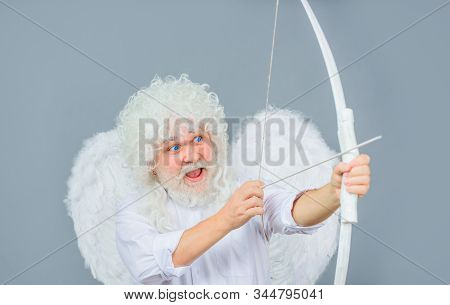 Cupid with bow and arrows. Love concept. Valentine angel. Handsome male angel Cupid. Bearded man with angel wings. Valentines day card. Valentines Day. Angel man with white wings. Valentines cupid. stock photo