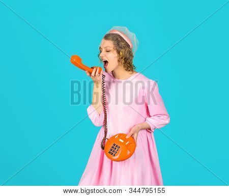 Happy woman holds handset. Young woman talking on retro phone. Smiling woman in pink dress with telephone handset. Pretty woman talking at retro handset. Girl talking on landline phone. Communication. stock photo