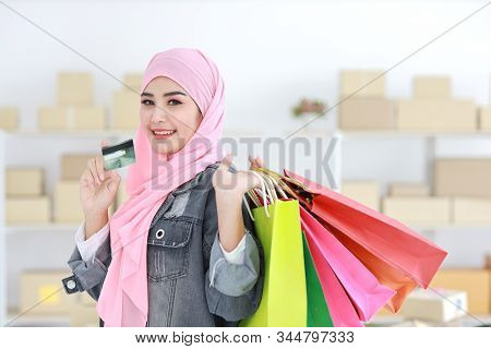 Active smart asian muslim woman in jean jacket standing and holding shopping bags while showing credit card with online package box delivery background. Beautiful girl looking at cemera and smile. stock photo