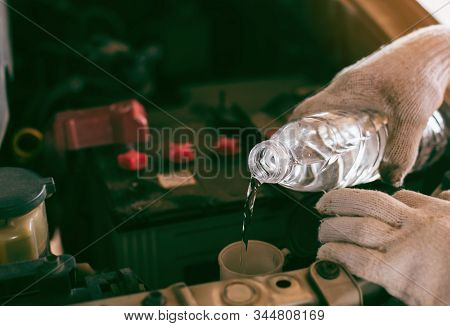 Man service mechanic maintenance inspection service maintenance car Check engine with fill water add water to the wiper car in garage showroom dealership blurred background For automotive automobile stock photo