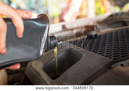 Pouring oil to car engine. Fresh oil poured during an oil change to a car. Hand mechanic in repairing car,Change the Oil stock photo