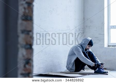 Unhappy guy in hood is sitting on cardboard on floor in abandoned building. Homeless sad man lost everything because of addiction. Social problems in society. Loneliness and depression concept. stock photo