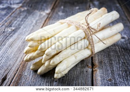 Raw white Asparagus with white head as bunch on an old rustic wooden board as closeup stock photo