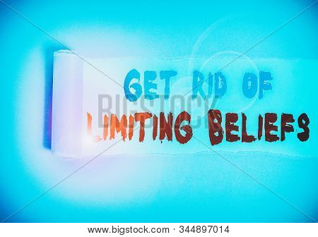 Handwriting text Get Rid Of Limiting Beliefs. Concept meaning remove negative beliefs and think positively Cardboard which is torn in the middle placed above a plain table backdrop. stock photo
