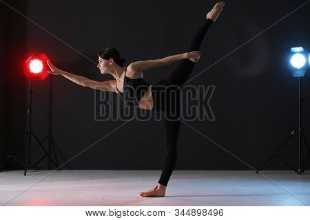 Young professional acrobat exercising in dark studio stock photo