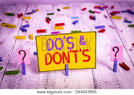 Text sign showing Do S And Don T S. Conceptual photo Confusion in one s is mind about something Scribbled and crumbling sheet with paper clips placed on the wooden table. stock photo