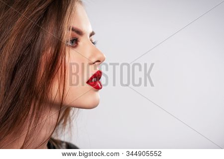Profile portrait of beautiful young woman with bright makeup. Beautiful brunette with bright red lipstick on her lips. Pretty girl with long brown hair. Model looking away stock photo
