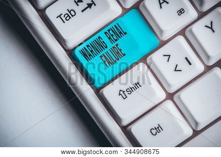 Writing note showing Warning Renal Failure. Business photo showcasing stop Filtering Excess Waste Acute Kidney malfunction White pc keyboard with note paper above the white background. stock photo
