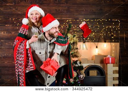 Man and woman santa claus hats cheerful celebrating new year. Celebrating winter holiday. Christmas fun. Interesting ideas celebration. Merry christmas. Guy piggybacking girl. Celebrating together stock photo