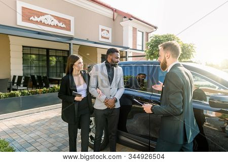 auto business, car sale, technology and people concept - business couple, African man and Caucasian woman with car dealer man standing near the black car in the yard of auto salon outdoors stock photo