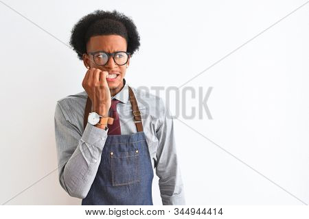 Young african american shopkeeper man wearing apron glasses over isolated white background looking stressed and nervous with hands on mouth biting nails. Anxiety problem. stock photo