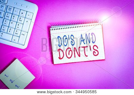 Text sign showing Do S And Dont S. Conceptual photo Rules or customs concerning some activity or actions Writing equipments and computer stuffs placed above classic wooden table. stock photo
