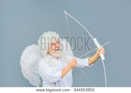 Love concept. Valentine angel. Handsome male angel Cupid. Bearded man with angel wings. Valentines day card. Valentines Day. Angel man with white wings. Cupid with bow and arrows. Valentines cupid. stock photo