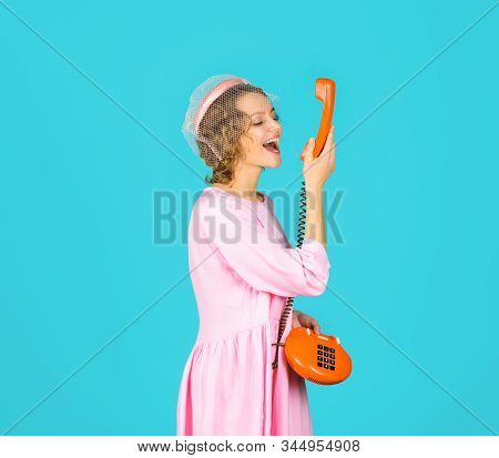 Happy woman talking on retro phone. Woman in pink dress with telephone handset. Happy woman holds handset. Pretty woman talking at retro handset. Girl talking on landline phone. Communication. stock photo