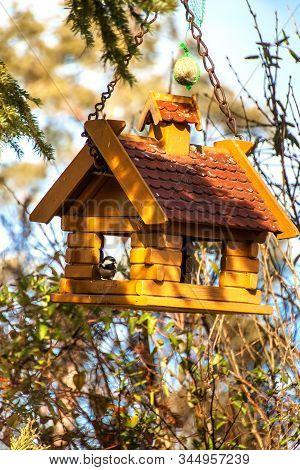 Garden Bird Feeder. Tree house for the birds, cheerful apartment. A self-made bird feeding house with a brown roof stock photo