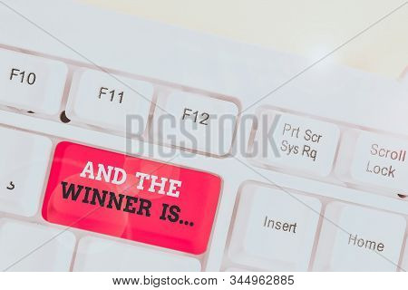 Handwriting text And The Winner Is. Concept meaning announcing a demonstrating or thing that wins something White pc keyboard with empty note paper above white background key copy space. stock photo