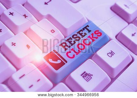 Text sign showing Reset Clocks. Conceptual photo To revisit return to or recreate a time or era from the past White pc keyboard with empty note paper above white background key copy space. stock photo