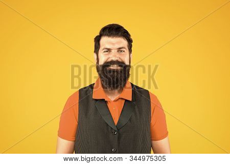 Restaurant cafe staff wanted. Man bearded hipster with mustache wear vest and shirt uniform yellow background. Shop staff concept. Salesman cashier career. Hiring shop store worker. Hospitality staff. stock photo