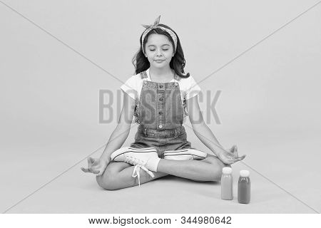Vegetarian smoothie drink. Yoga training. KId girl sit meditate. Meditating practice. Good vibes. Peaceful meditating. Learn meditating techniques. Stay positive and optimistic. Healthy way of life. stock photo