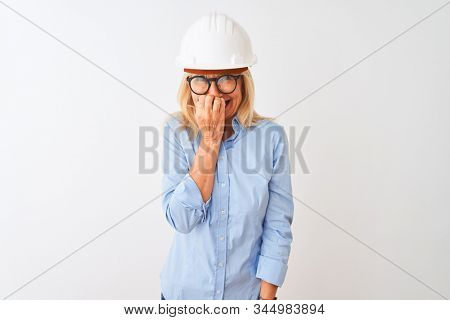 Middle age architect woman wearing glasses and helmet over isolated white background looking stressed and nervous with hands on mouth biting nails. Anxiety problem. stock photo