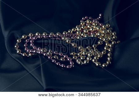 Mardi Gras beads on a black background. Carnival accessory stock photo