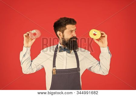 Sweet donut. Waiter in cafe. Doughnut calories. Glazed donut. Bearded well groomed man in apron selling donuts. Donut food. Baked goods. Sweets and cakes. Junk food. Hipster bearded baker hold donuts. stock photo
