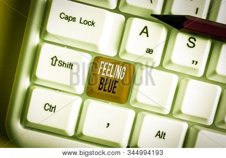 Handwriting text Feeling Blue. Concept meaning Feeling of desperation because of sadness or missing someone White pc keyboard with empty note paper above white background key copy space. stock photo