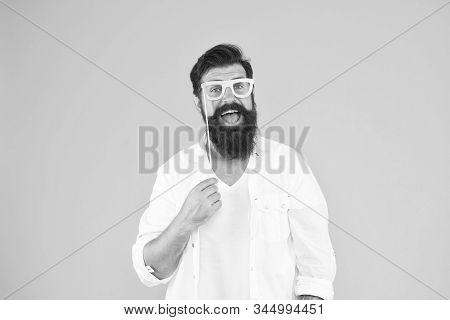 Bearded man happy to join party. Guy with beard and mustache hold eyeglasses photo booth prop. Party accessory. Good mood. Holiday celebration. Smart nerd eyeglasses. Last minute costume party ideas. stock photo