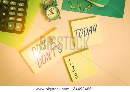 Text sign showing Do S And Don T S. Conceptual photo Confusion in one s is mind about something Wire mouse portable calculator notepads paper sheets clips color background. stock photo