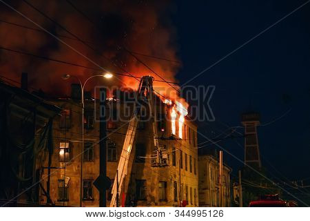 Night fire at roof in building, burning house with smoke, Fire disaster. stock photo