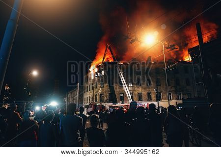 Burning city building at night, Firefighters extinguish house, Silhouettes of citizens people on foreground looks and flaming fire with smoke. stock photo