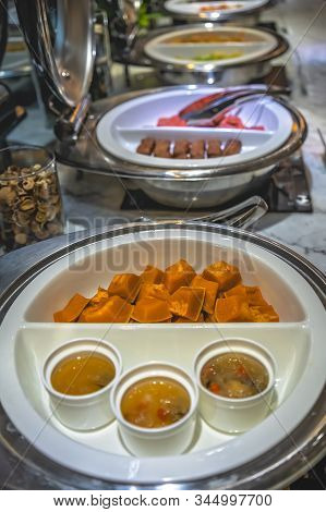 Cut in chunks buternut squash and spicy sauce in a serving bowls as part of an asian style breakfast buffet on the table in hotel cafeteria, China stock photo