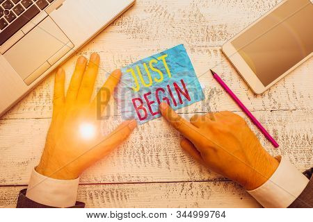 Conceptual hand writing showing Just Begin. Business photo text to start to happen Begin to do something in business or a job Hand hold note paper near writing equipment and smartphone. stock photo