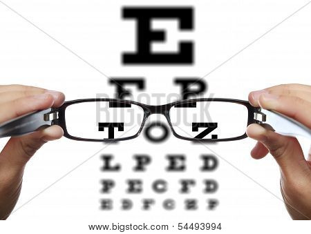 Glasses in hands in front of eye test stock photo