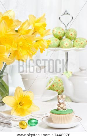Festive Easter table setting with freshly picked spring daffodils and bunny cupcake stock photo