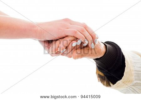 Elderly hands held by a young person - helping concept. stock photo