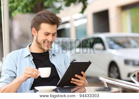 Happy man reading an ebook or tablet in a coffee shop terrace holding a cup of tea stock photo