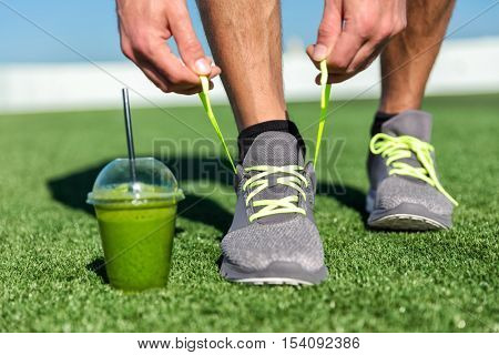 Green smoothie fitness man lacing running shoes, Athlete runner with green vegetable detox juice get