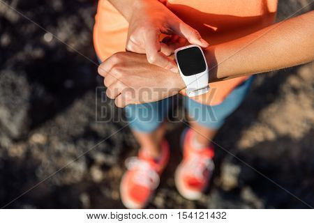 Trail runner athlete using her smart watch app to monitor fitness progress or heart rate during run