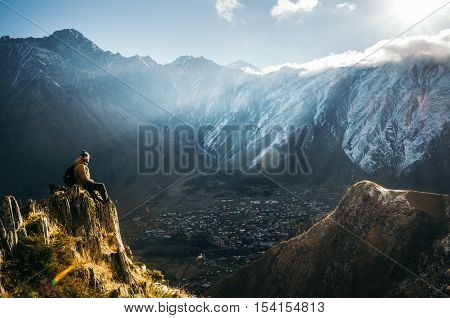Young tourist in bright hat black trousers with a backpack sit on cliff's edge and looking at the misty mountain village and glacier at sunrise Stepantsminda Georgia