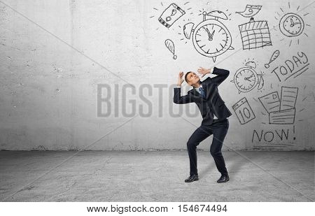 A frightened businessman shielding himself with his hands from the drawings of calendars and clocks on the grey wall. Business and time-management. Organizing and planning. Productivity and efficiency.