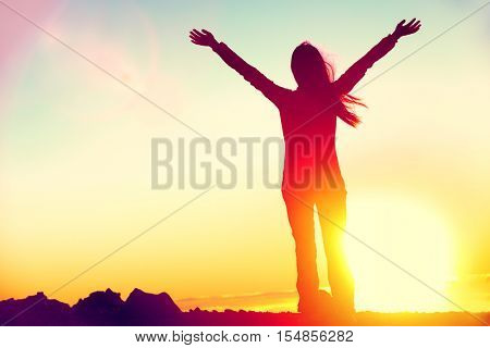 Happy celebrating winning success woman at sunset or sunrise standing elated with arms raised up abo