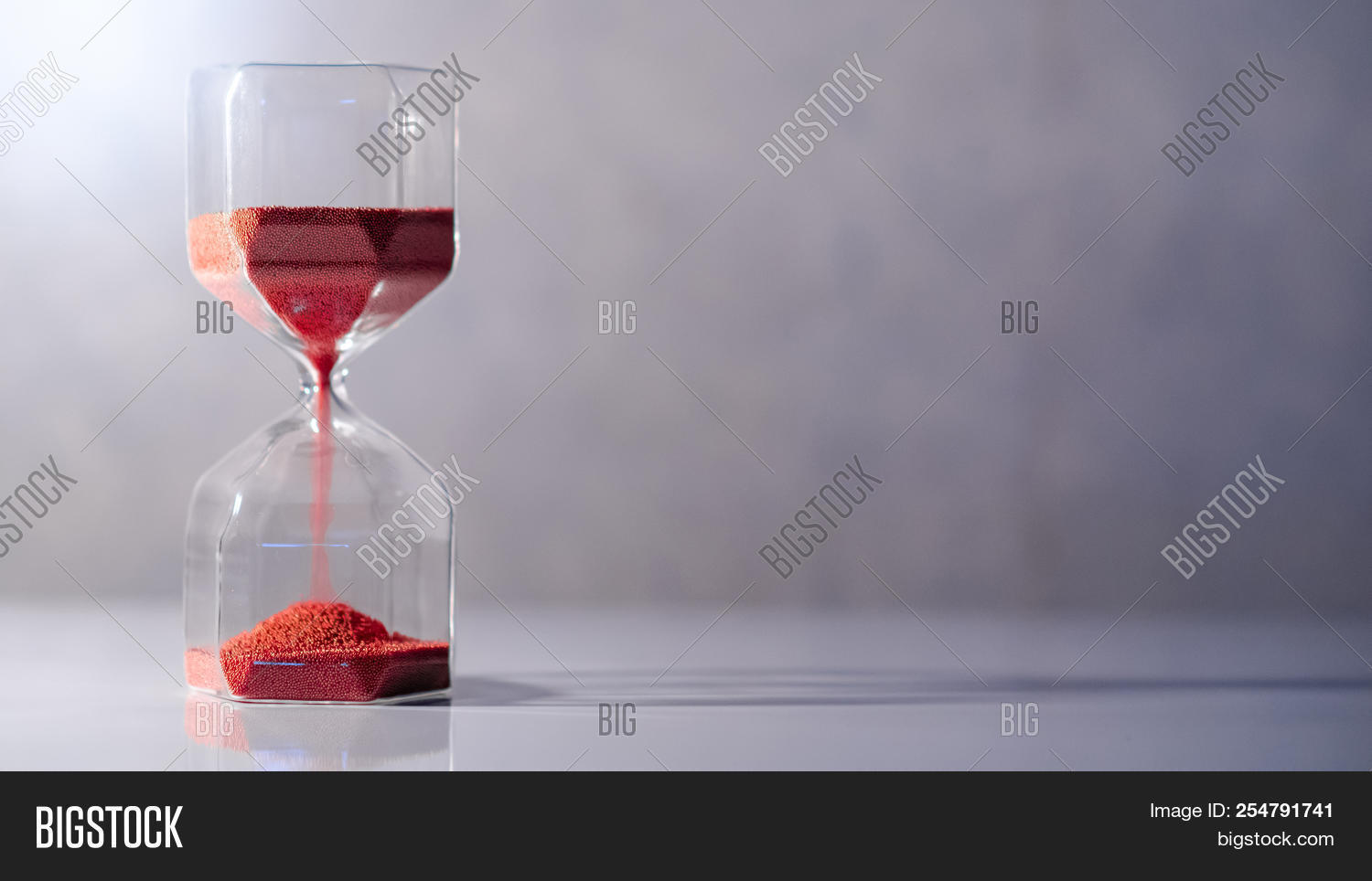 Red Sand Running Through The Shape Of Modern Hourglass On White Table.time Passing And Running Out O