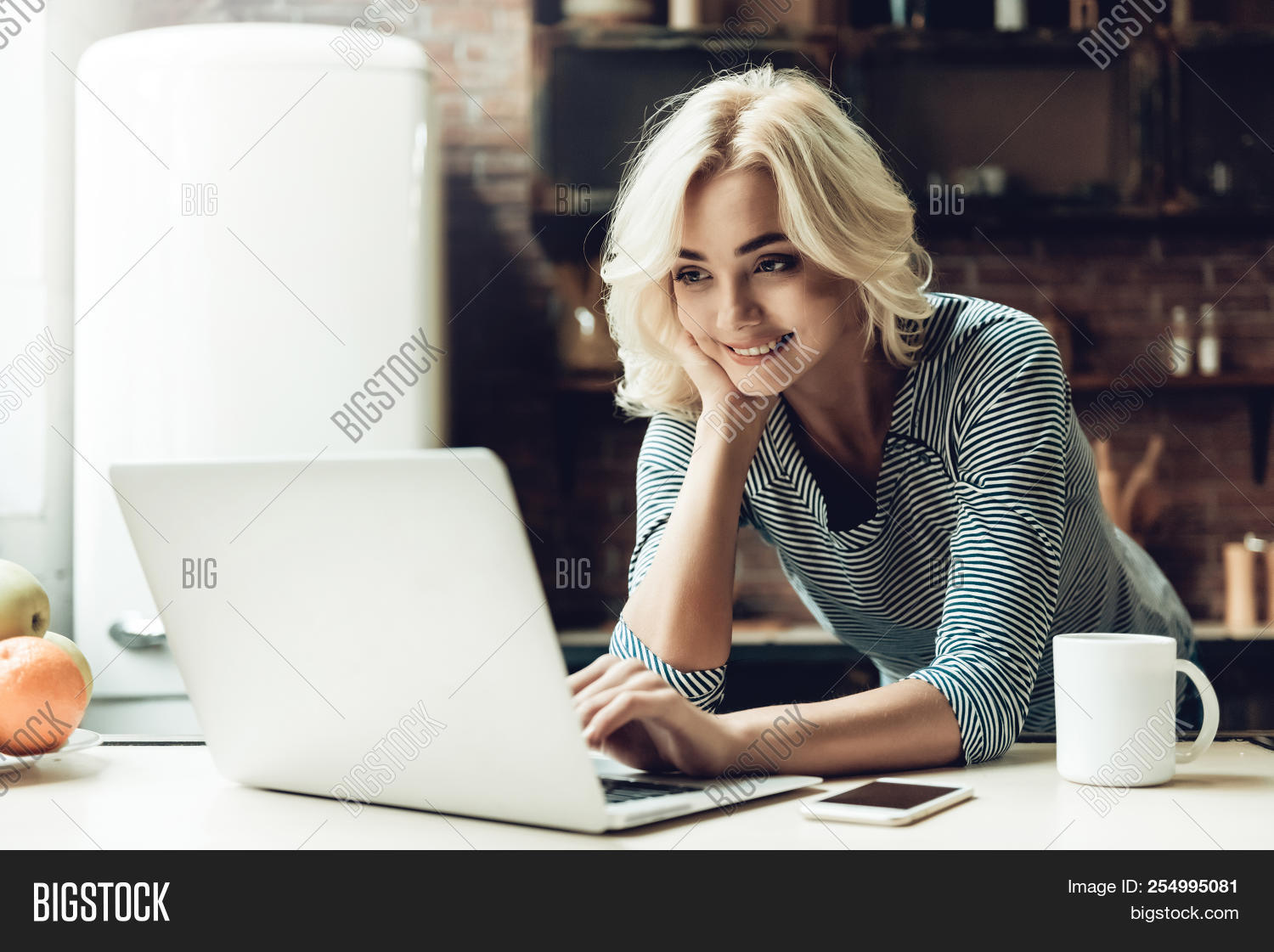 Young Smiling Beautiful Woman Using Laptop At Home. Portrait Of Young Attractive Girl Serfing Intern