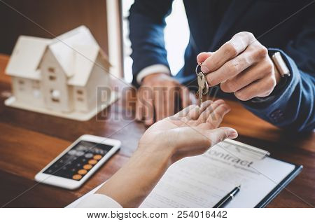 Real Estate Agent Sales Manager Holding Filing Keys To Customer After Signing Rental Lease Contract