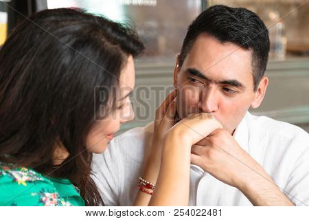 Man looks in eyes of his wife and kisses her hand stock photo
