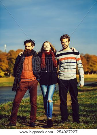Young People Friends Of Pretty Girl And Two Bearded Men Outdoors In Park On Autumn Day On Natural Ba