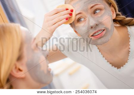 Beauty procedures spa and skin care concept. Young woman looking in mirror, removing facial clay mud mask with sponge in bathroom stock photo