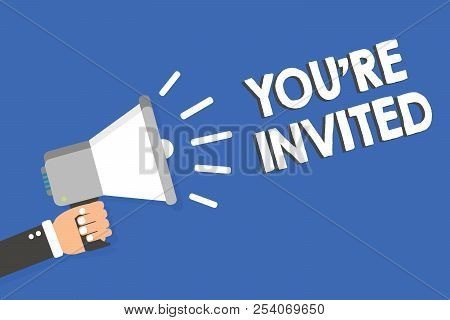 Text sign showing You re are Invited. Conceptual photo Please join us in our celebration Welcome Be a guest Man holding megaphone loudspeaker blue background message speaking loud. stock photo